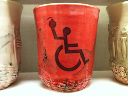 "A ceramic mug with the ""disabled"" signage of a stick figure wheelchair user throwing a bomb."