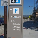 Sign that points the way to Bart, bike lane, parking and the campus.